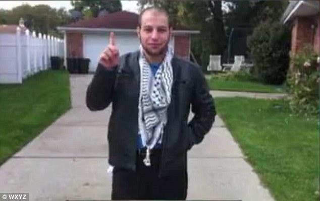 Khalil Abu-Rayyan making the ISIS gesture wearing the keffiyeh, iconic of jihad.
